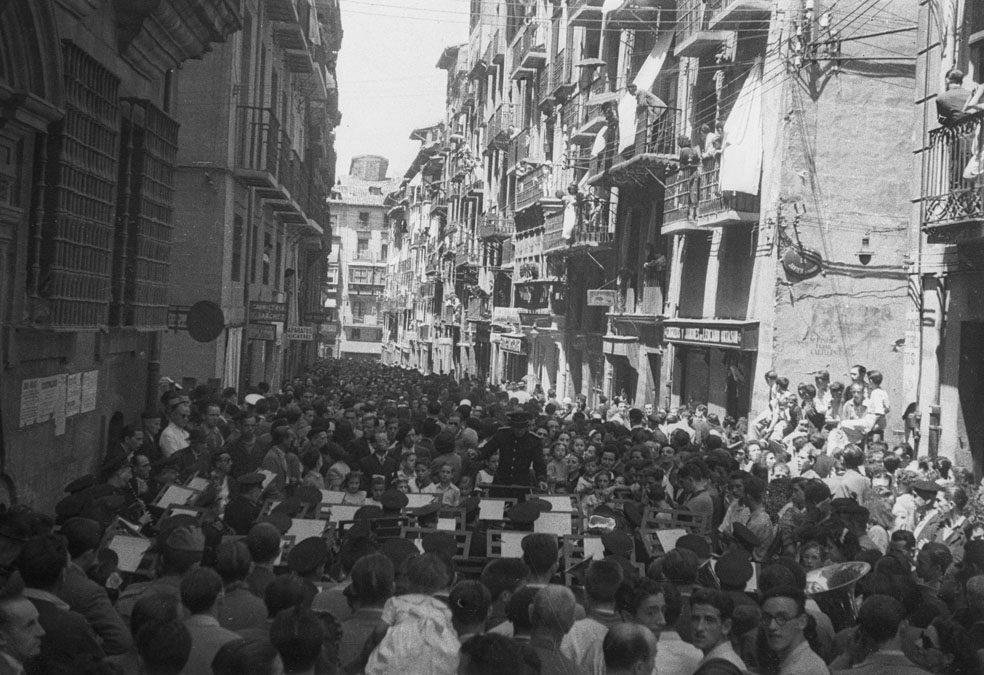 Imagen en blanco y negro de un multitudinario concierto de la Pamplonesa en la calle Estafeta.